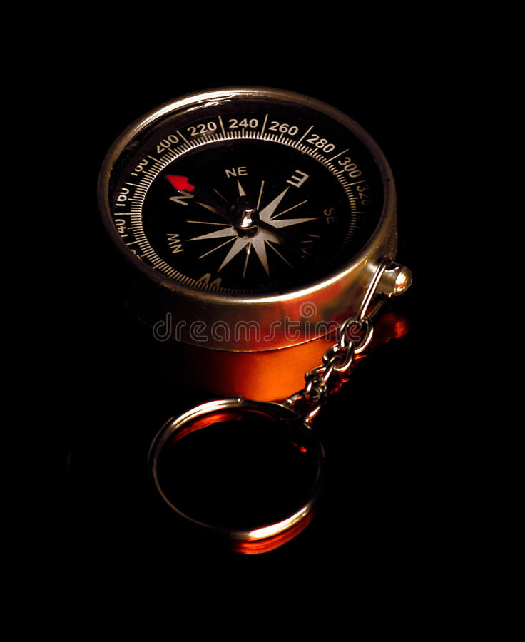 Compass. Metal compass on black background and reddish reflection stock photography