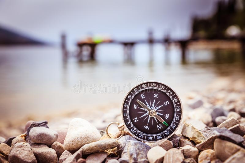 Compass on the beach, small stones, text space. Close up of a nautical compass on the beach, coastline in the blurry background path travel adventure concept royalty free stock image
