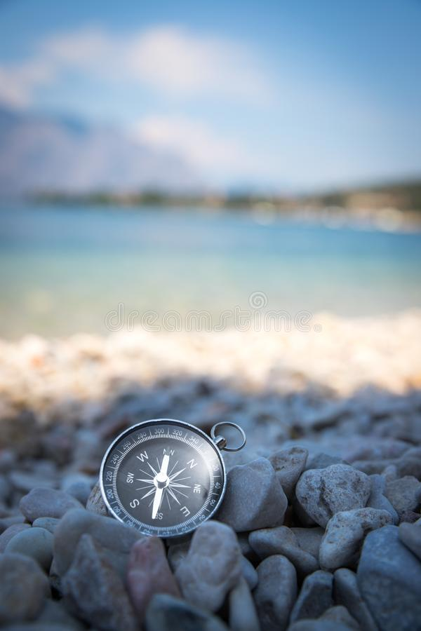 Compass on the beach, small stones, text space. Navigation: close up of a compass lying on a pebble beach path travel adventure concept paradise blue target stock image