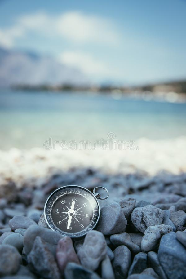 Compass on the beach, small stones, text space. Navigation: close up of a compass lying on a pebble beach path travel adventure concept paradise blue target royalty free stock photography