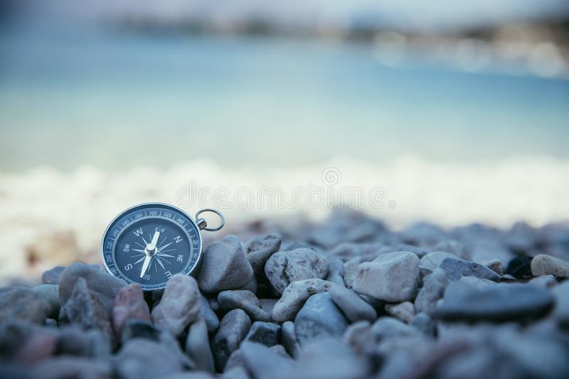Compass on the beach, small stones, text space. Navigation: close up of a compass lying on a pebble beach path travel adventure concept paradise blue target stock photo