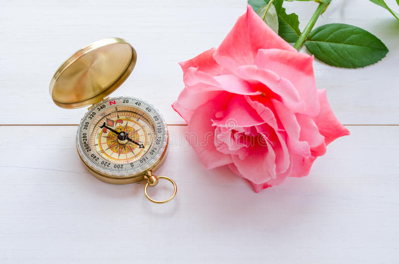 Compass with beautiful pink rose on a white wooden background royalty free stock image