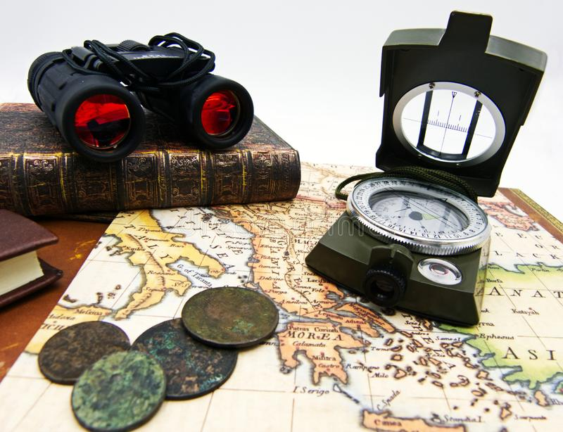 Compass, binoculars and old book on vintage map, white background royalty free stock images
