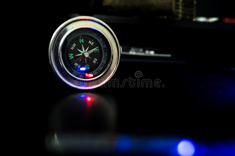 Compass with blue light falling on it. stock photography