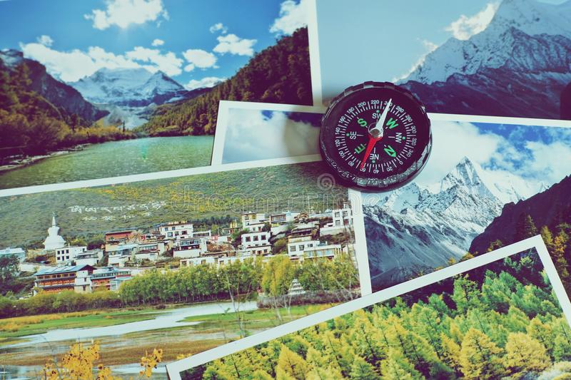 Compass on blur nature photograph of popular tourist destination in autumn background, China traveling concept. Compass on blur colorful nature photograph of stock photography