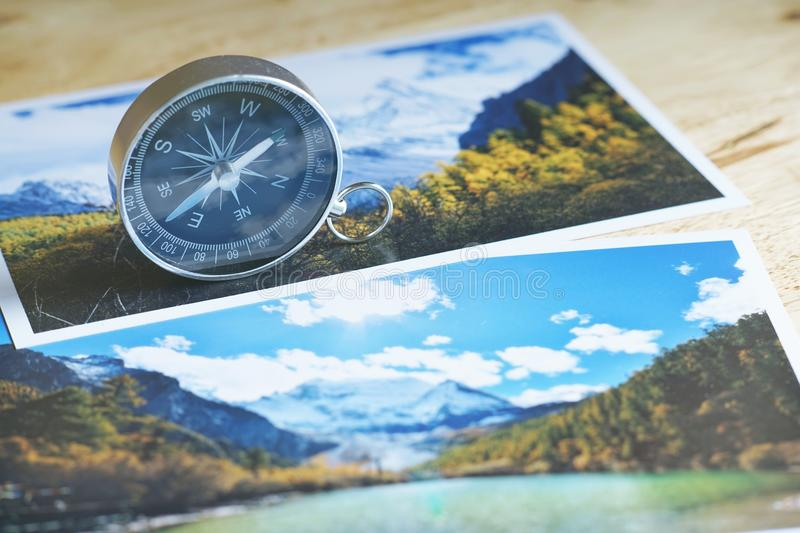 Compass on blur nature photograph of popular tourist destination in autumn background, China traveling concept. Compass on blur colorful nature photograph of stock photo
