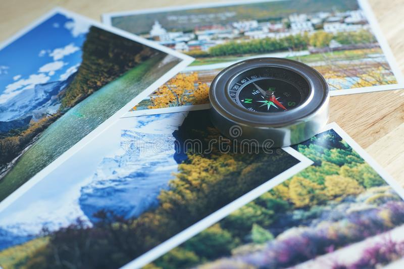 Compass on blur nature photograph of popular tourist destination in autumn background, China traveling concept. Compass on blur colorful nature photograph of stock photos