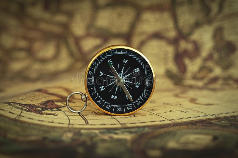 Compass on blur vintage map background, retro color tone, direction journey planning concept, blank space, top view. Copy space stock photography