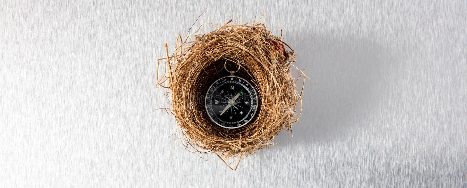 Compass in comfortable nest for safe travel or insured adventure stock photos