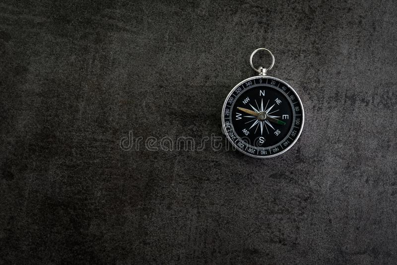 Compass on dark black textured cement with copy space using as d stock image