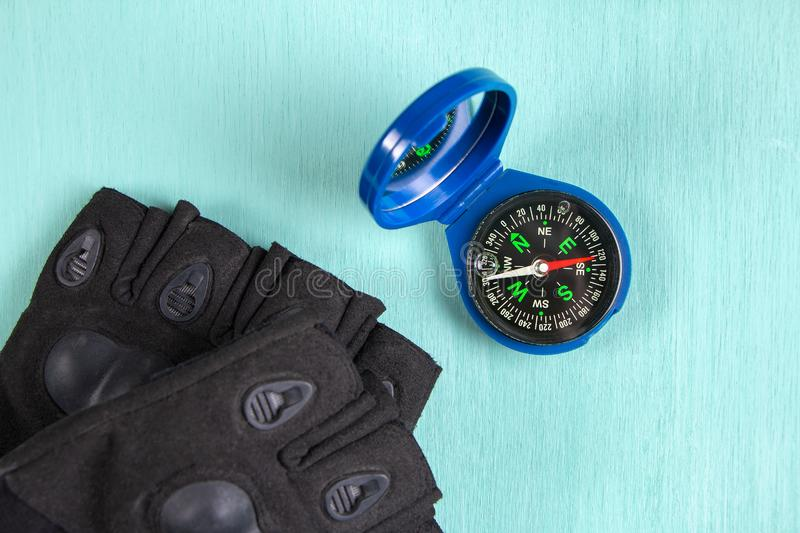 Compass and gloves on green background. Top view royalty free stock photography