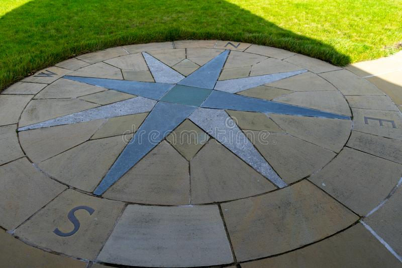A compass on the ground made in paving stones showing north south east and west. Laid in paving stones stock photos