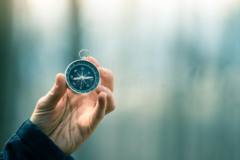 Compass holding in the hand, outdoor adventure. Man on an adventure is holding a compass in his hand for finding is route travel concept target symbol instrument royalty free stock images