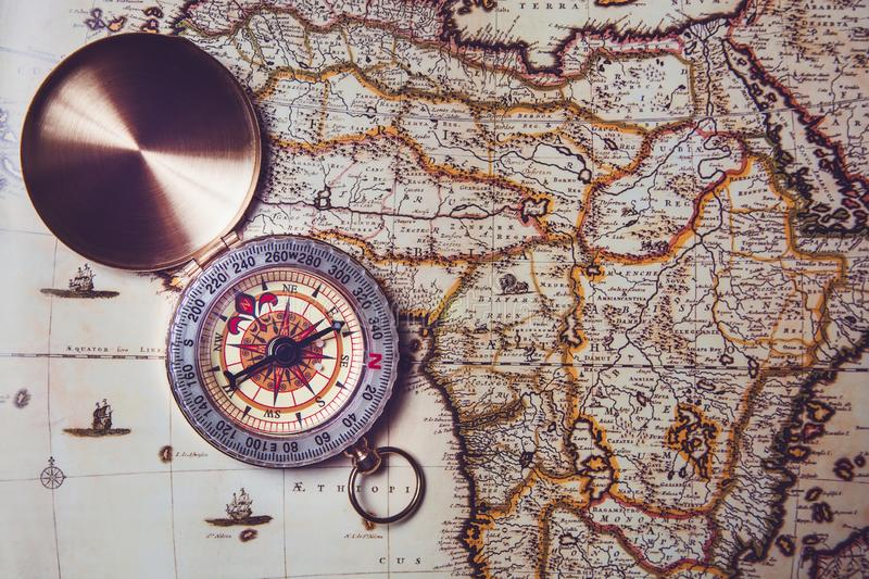 Compass lies on an old map. Orientation on the ground by compass stock image