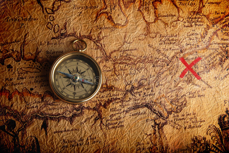 Compass and a map. Old brass compass lying on a very old map showing the way to treasure
