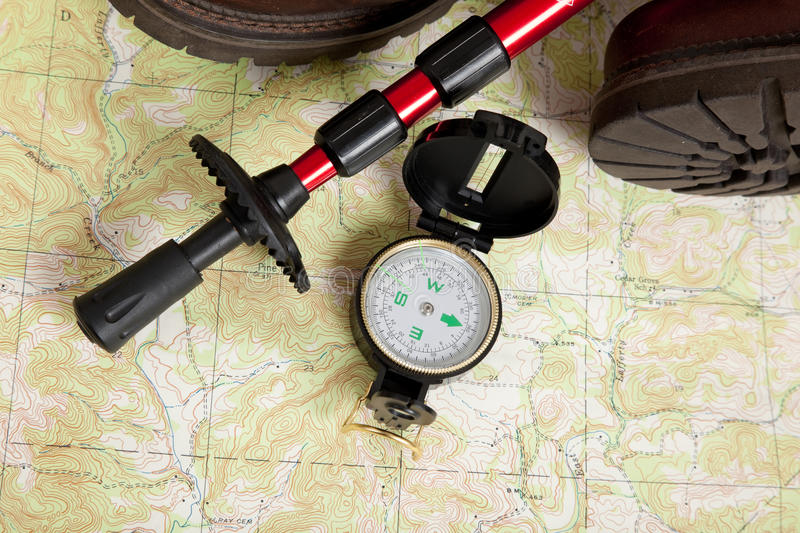 Compass on a map with a hiking stick and boots. Compass laying on a topographical map with a hiking stick and boots royalty free stock images