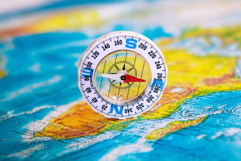 Compass on map. The magnetic compass is located on a geographic map. Satellites adventure. Travel concept. royalty free stock image