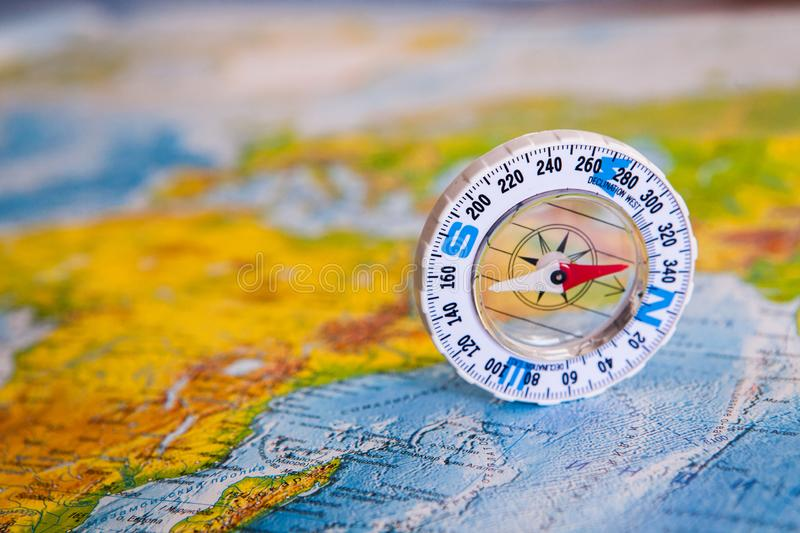 Compass on map. The magnetic compass is located on a geographic map. Satellites adventure. Travel concept. stock images