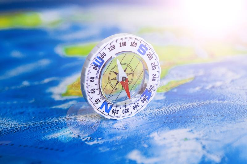 Compass on map. The magnetic compass is located on a geographic map. Satellites adventure. Travel concept. stock photography