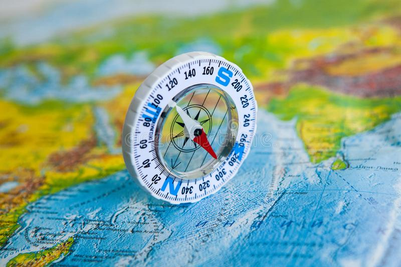 Compass on map. The magnetic compass is located on a geographic map. Satellites adventure. Travel concept. stock photo