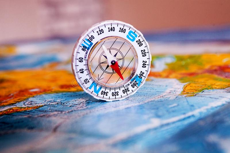 Compass on map. The magnetic compass is located on a geographic map. Satellites adventure. Travel concept. stock image