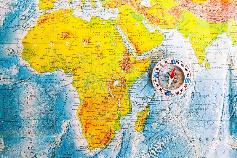 Compass on map. The magnetic compass is located on a geographic map. Satellites adventure. Travel concept. stock photos