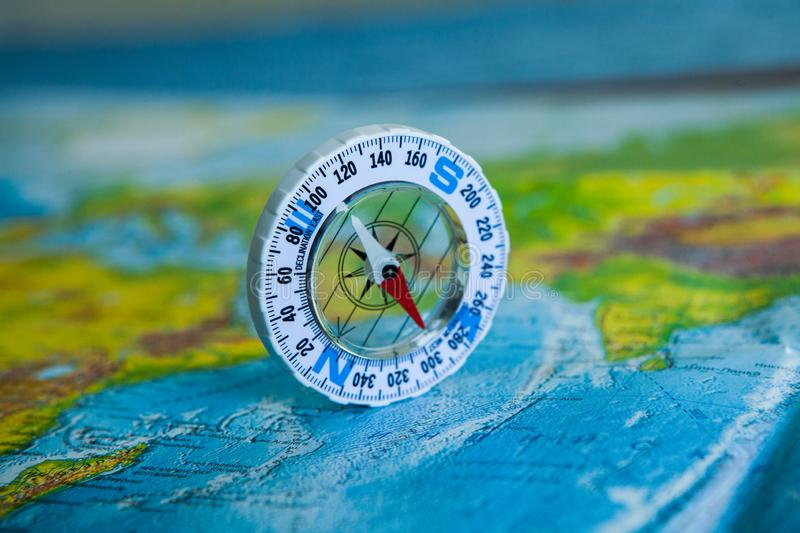 Compass on map. The magnetic compass is located on a geographic map. Satellites adventure. Travel concept. royalty free stock photo