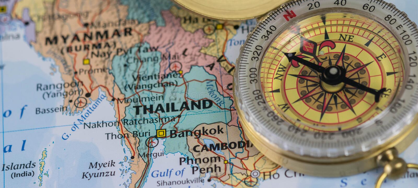 Compass on a close up map pointing at Thailand and planning a travel destination. Compass on a map pointing at Thailand and planning a travel destination stock photo