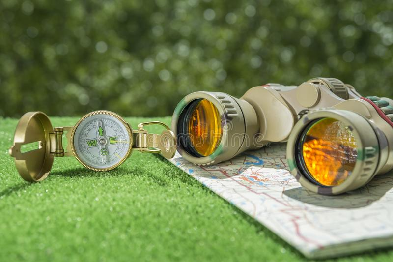 Compass old map and binoculars on grass and greens background. royalty free stock photo