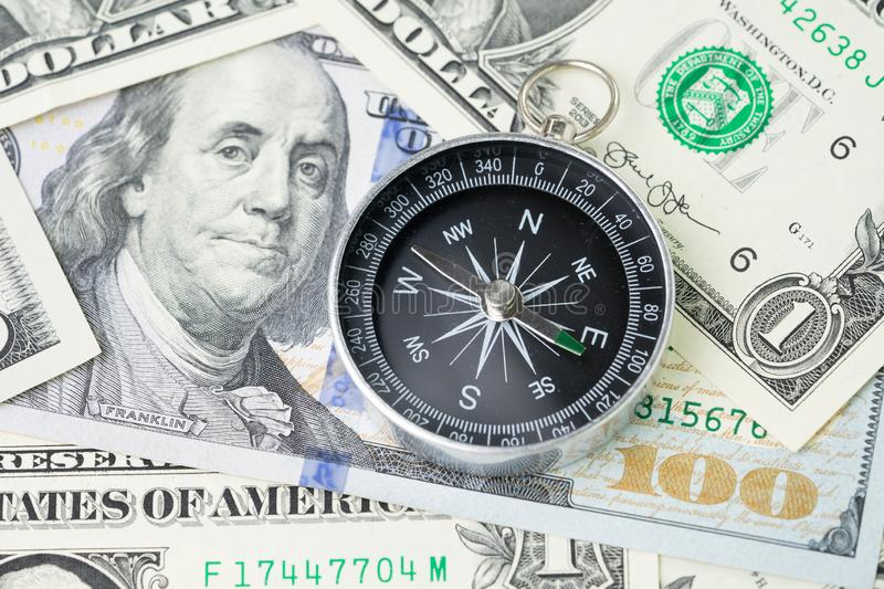 Compass and pile of US dollar money banknote, investment, financial crisis or economic direction concept stock photography