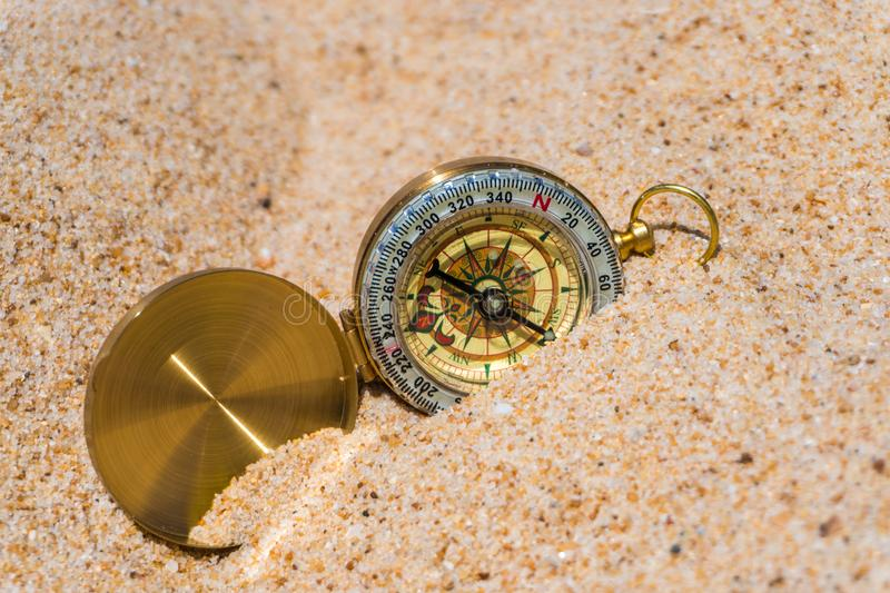 Compass in the gold sand on the beach. Summer time royalty free stock photography