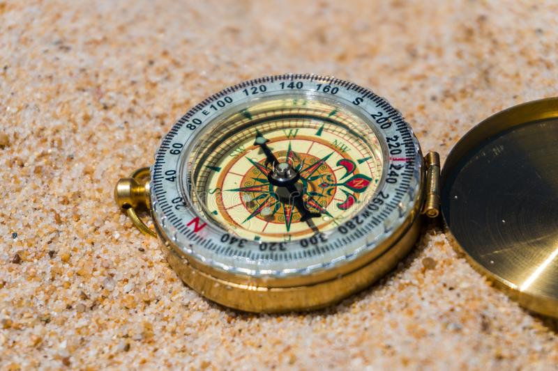 Compass in the sand on the beach. summer time stock image