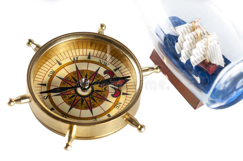 A compass and ship in a bottle on white stock photography