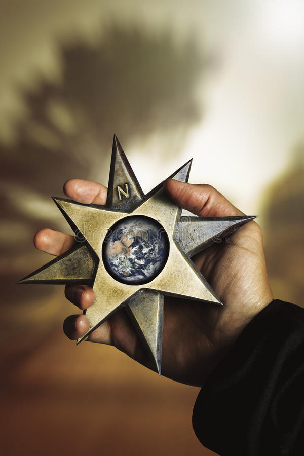 Hand holding compass star wind rose with earth. Compass star windrose with planet earth in hand. A hand holding a big compass star shape with directional stock photography