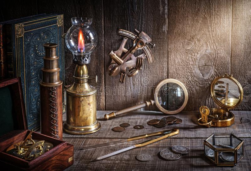 Compass, telescope, sextant, coin, divider and old book on wood desk stock photography