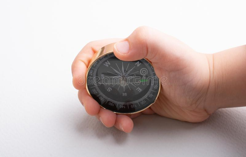 Compass tool in hand on white. Compass tool in toddler hand on white royalty free stock image