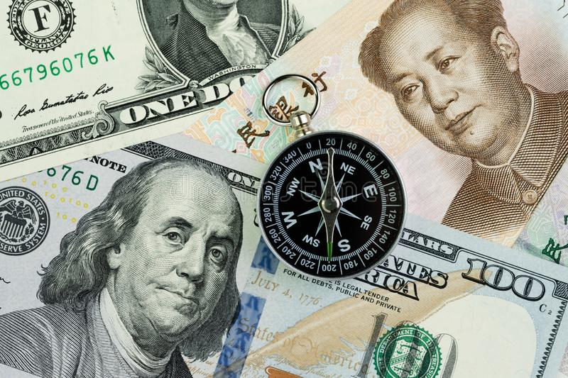 Compass on US America Dollar and Chinese Yuan banknotes using as tariff or trade war negotiation or future direction between the stock photos