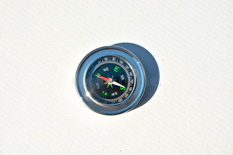 Compass on white. Magnetic navigation tool for orienteering royalty free stock photos