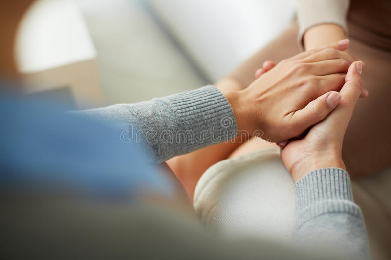 Compassion. Close-up of psychiatrist hands together holding palm of her patient royalty free stock image