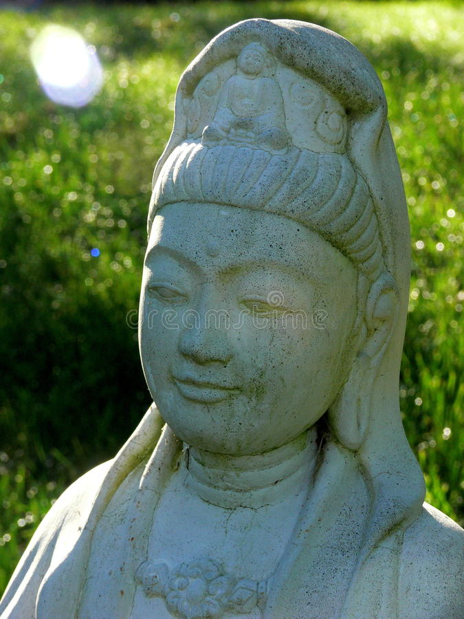 Compassion: smiling Kuan Yin with sunbeam. Buddhist icon of compassion Kuan Yin in grassy sunlit field royalty free stock images
