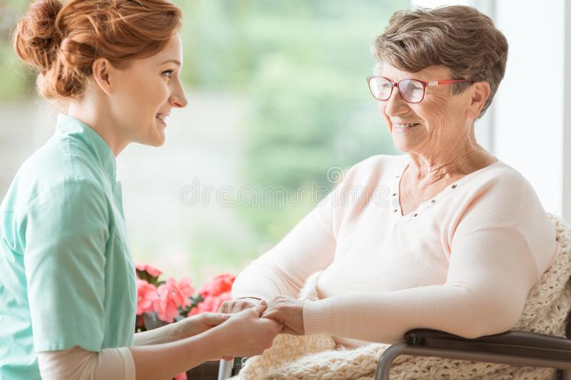Compassionate nurse explaining a geriatric handicapped patient w. Ith dementia medical procedures while holding her hands. Assisted living house for pensioners stock photography