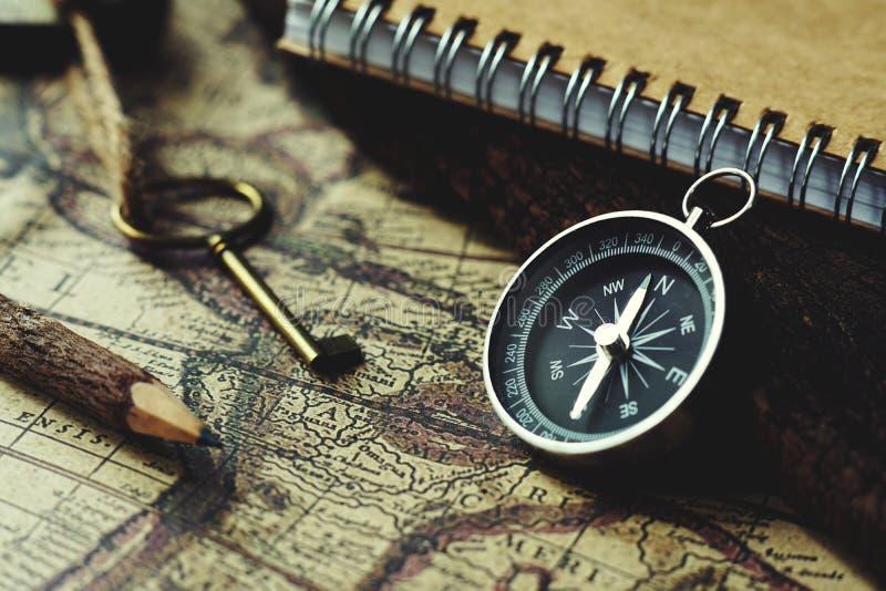 Compasso, chave, lápis e livro no fundo do mapa do vintage do borrão, tom clássico retro da cor, espaço da cópia foto de stock royalty free