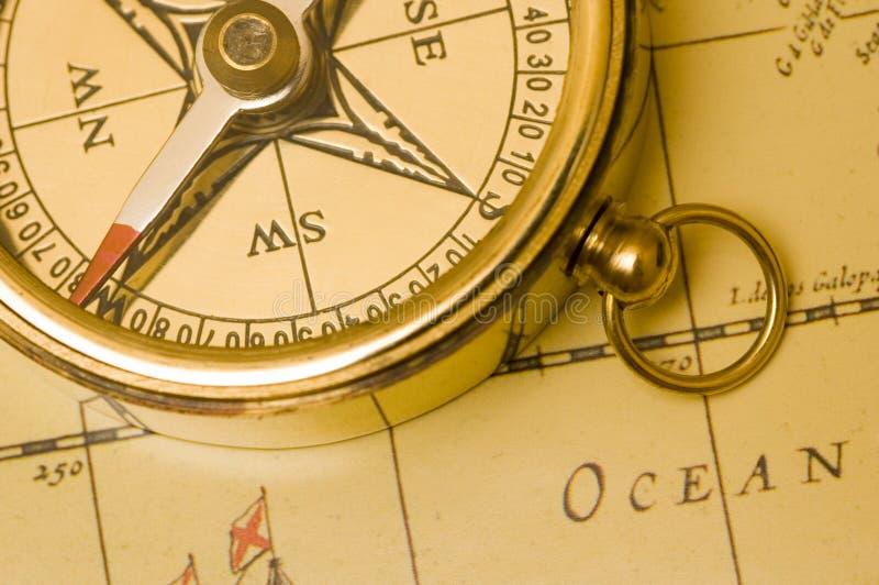 Compasso de bronze do estilo velho em um mapa fotografia de stock