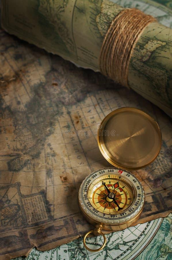 Compasso de bronze do vintage e mapas velhos imagem de stock