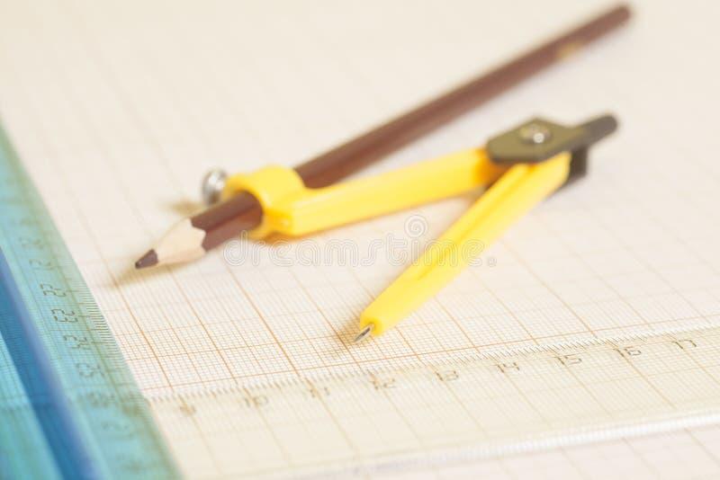 Compasso de desenho amarelo com pensil e réguas no papel de gráfico en imagens de stock