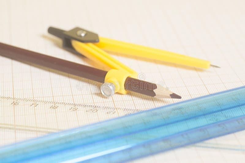 Compasso de desenho amarelo com pensil preto e réguas no pa do gráfico foto de stock