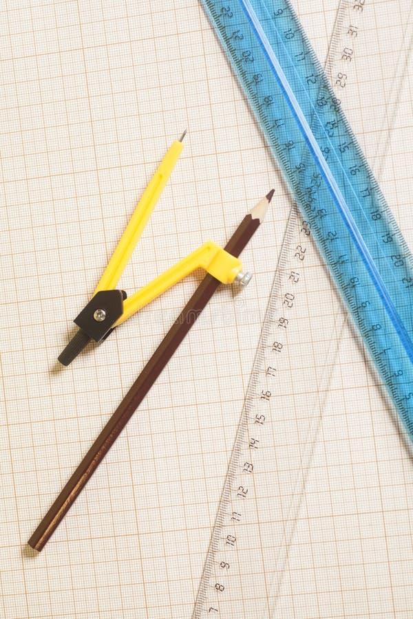 Compasso de desenho amarelo com pensil preto e réguas no pa do gráfico imagem de stock