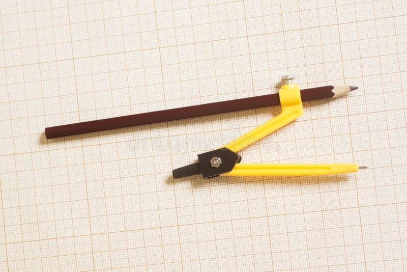 Compasso de desenho amarelo no papel de gráfico fotos de stock royalty free