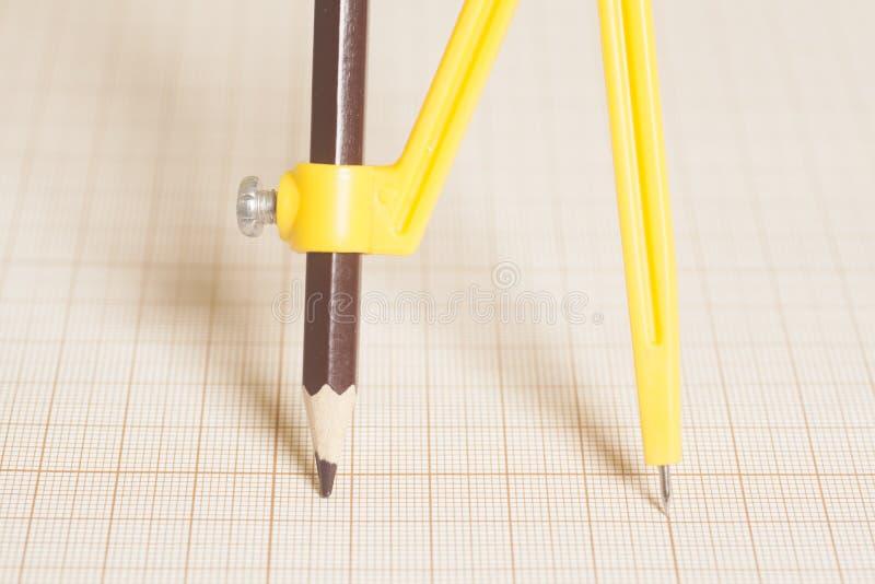 Compasso de desenho amarelo no papel de gráfico imagens de stock royalty free
