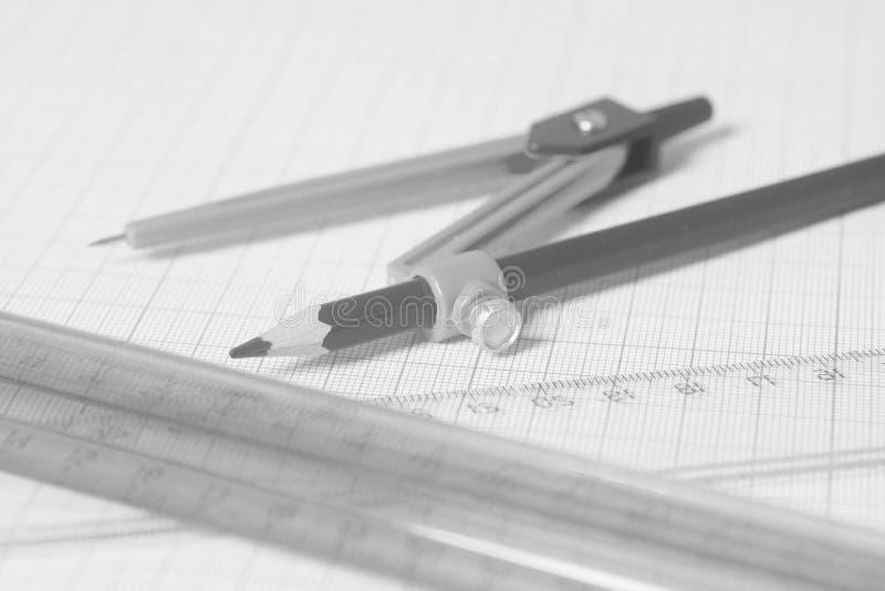 Compasso de desenho com pensil preto e réguas no papel de gráfico fotografia de stock royalty free